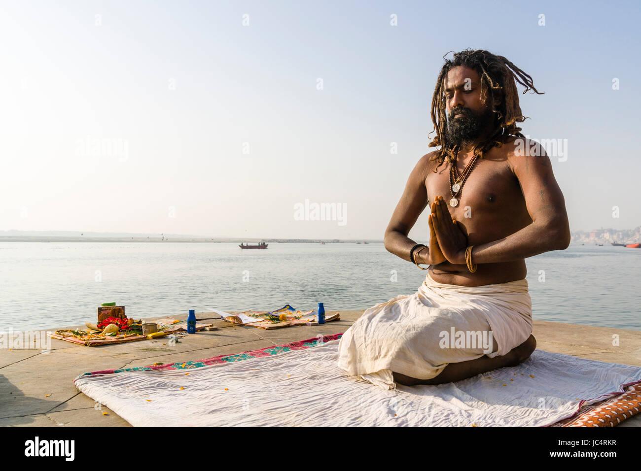 Ein sadhu, heiliger Mann, sitzt und Beten auf einer Plattform am heiligen Fluss Ganges Meer Ghat im Vorort godowlia Stockbild