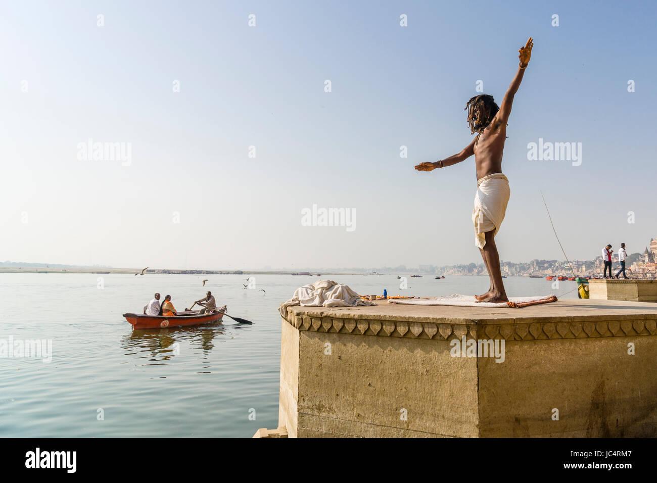Ein sadhu, heiliger Mann, tanzt auf einer Plattform am heiligen Fluss Ganges Meer Ghat im Vorort godowlia Stockbild