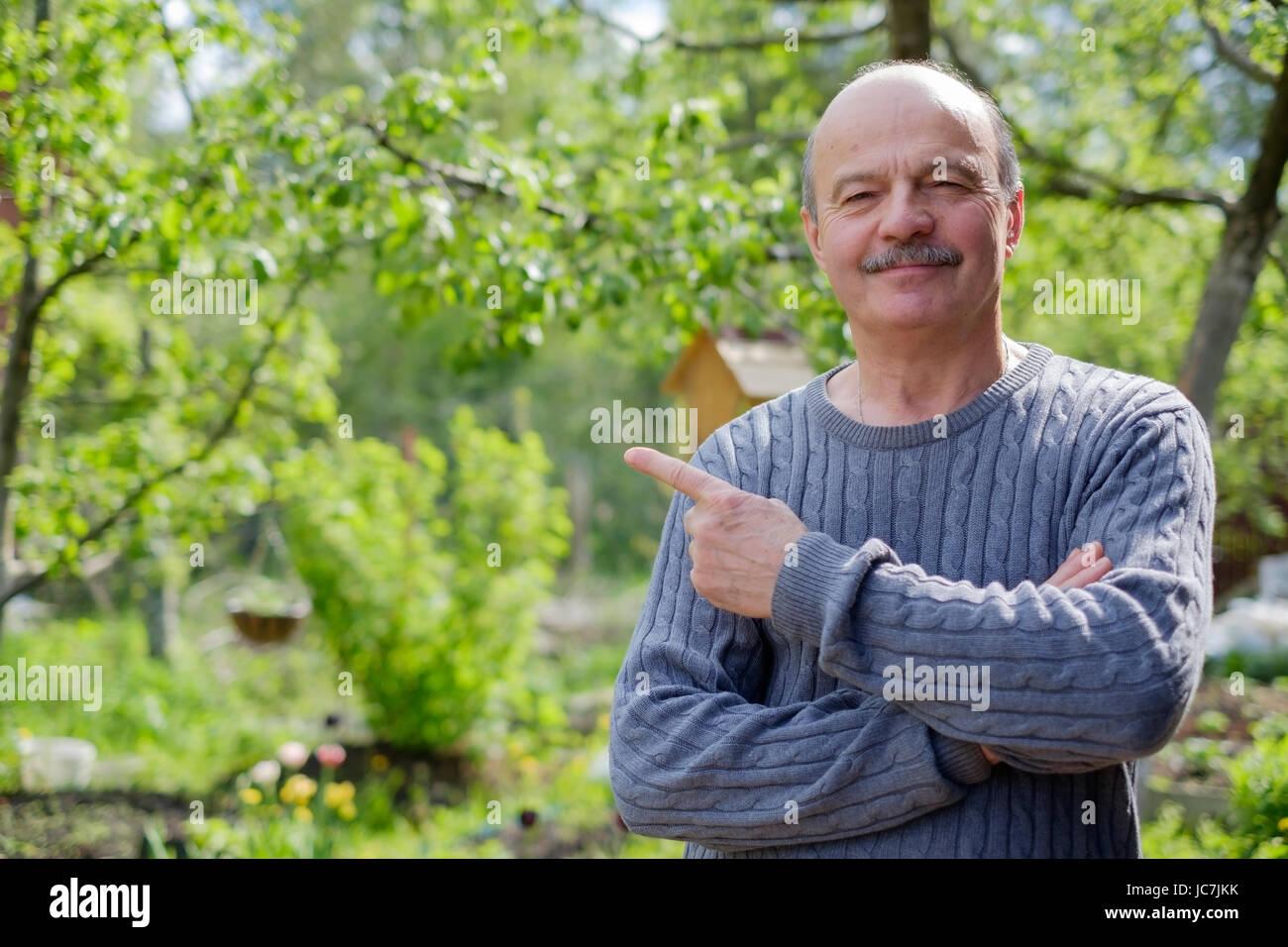 Reifer Mann sitzen im Garten in der Nähe von Apfelbaum im Lande. Er zeigt Zeigefinger beiseite. Stockbild