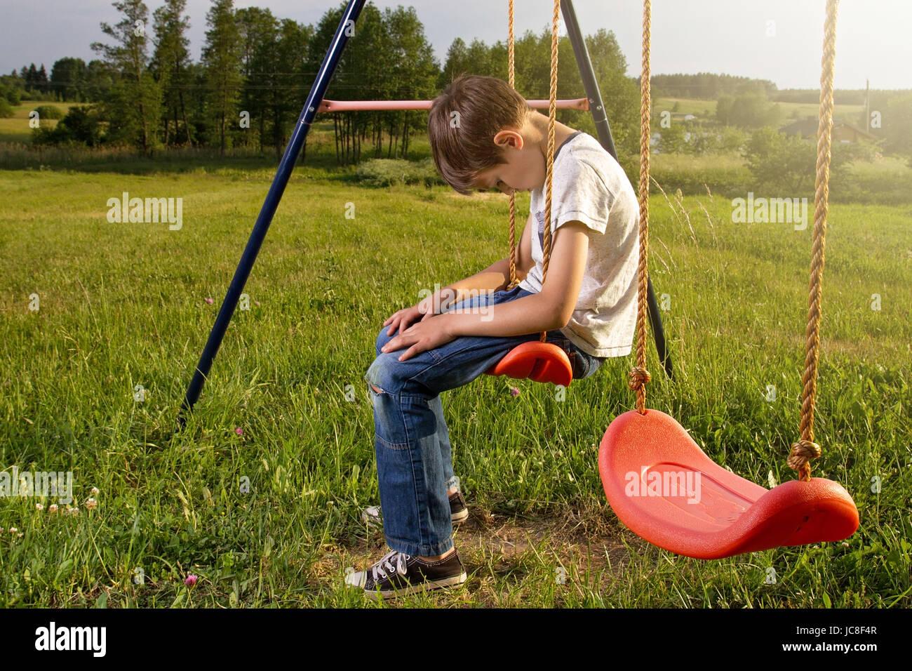 Traurig einsam Junge sitzt auf Schaukel allein