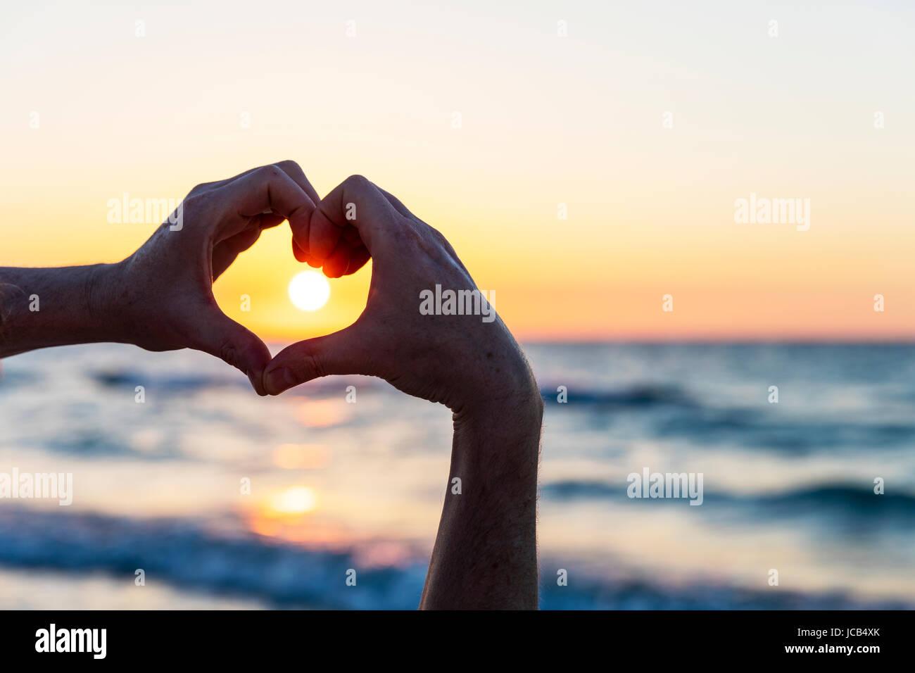 Hände, so dass eine Herzform vor der Sonne Stockbild