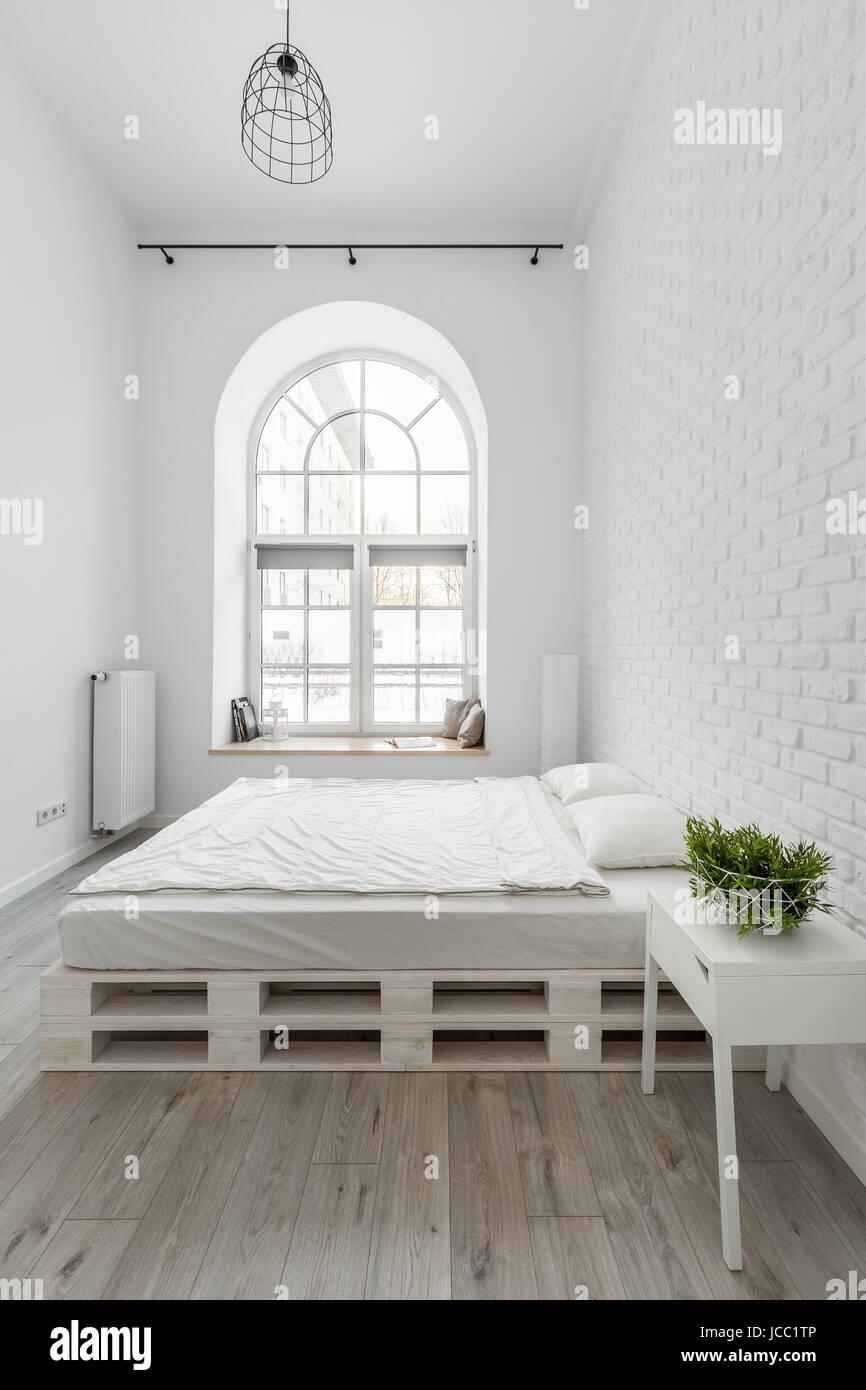 Weißes Schlafzimmer mit Bett und Ziegel Wand Palette Stockfoto, Bild ...