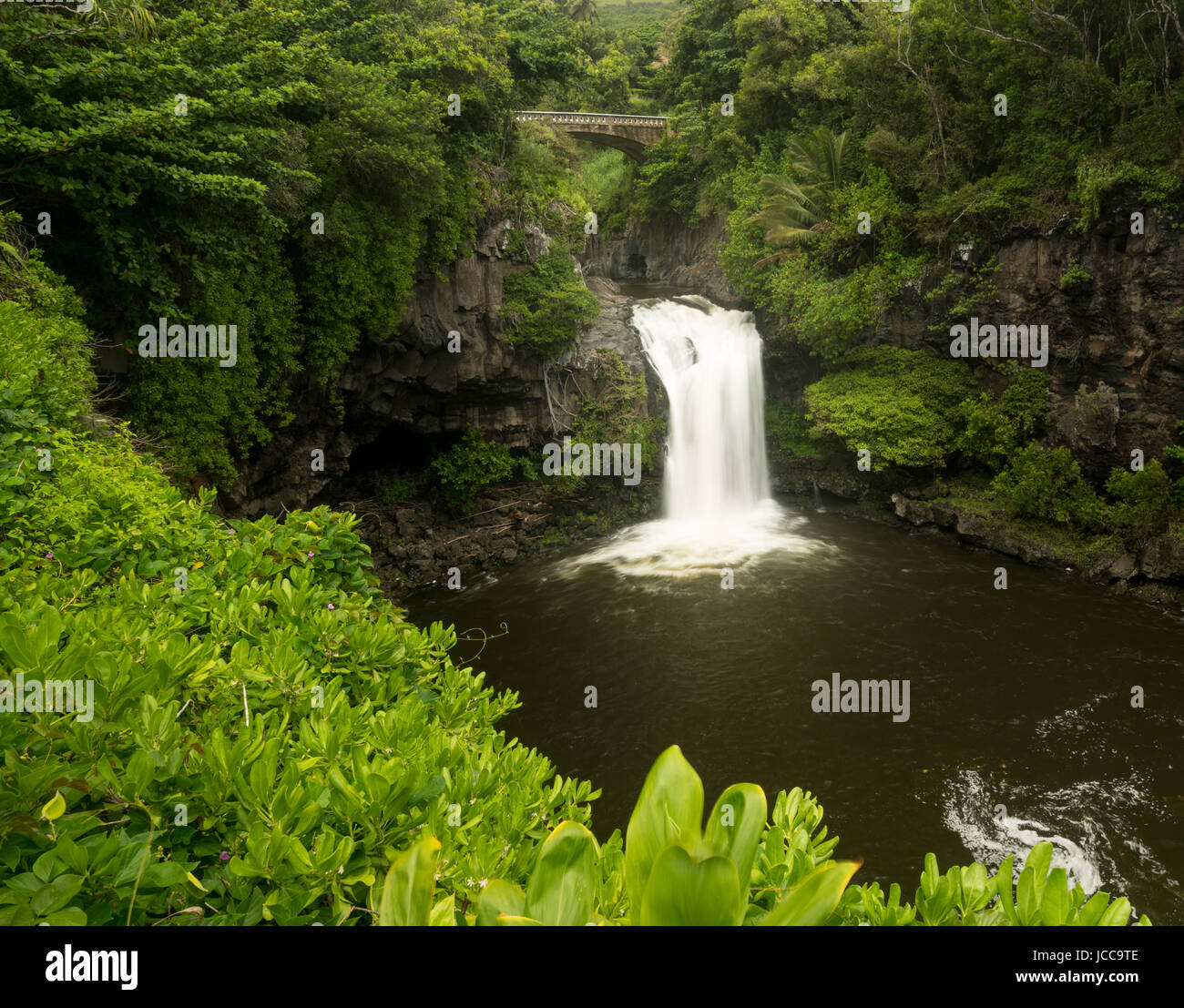 Wasserfall unter Straßenbrücke bei sieben heiligen Pools Maui Stockfoto