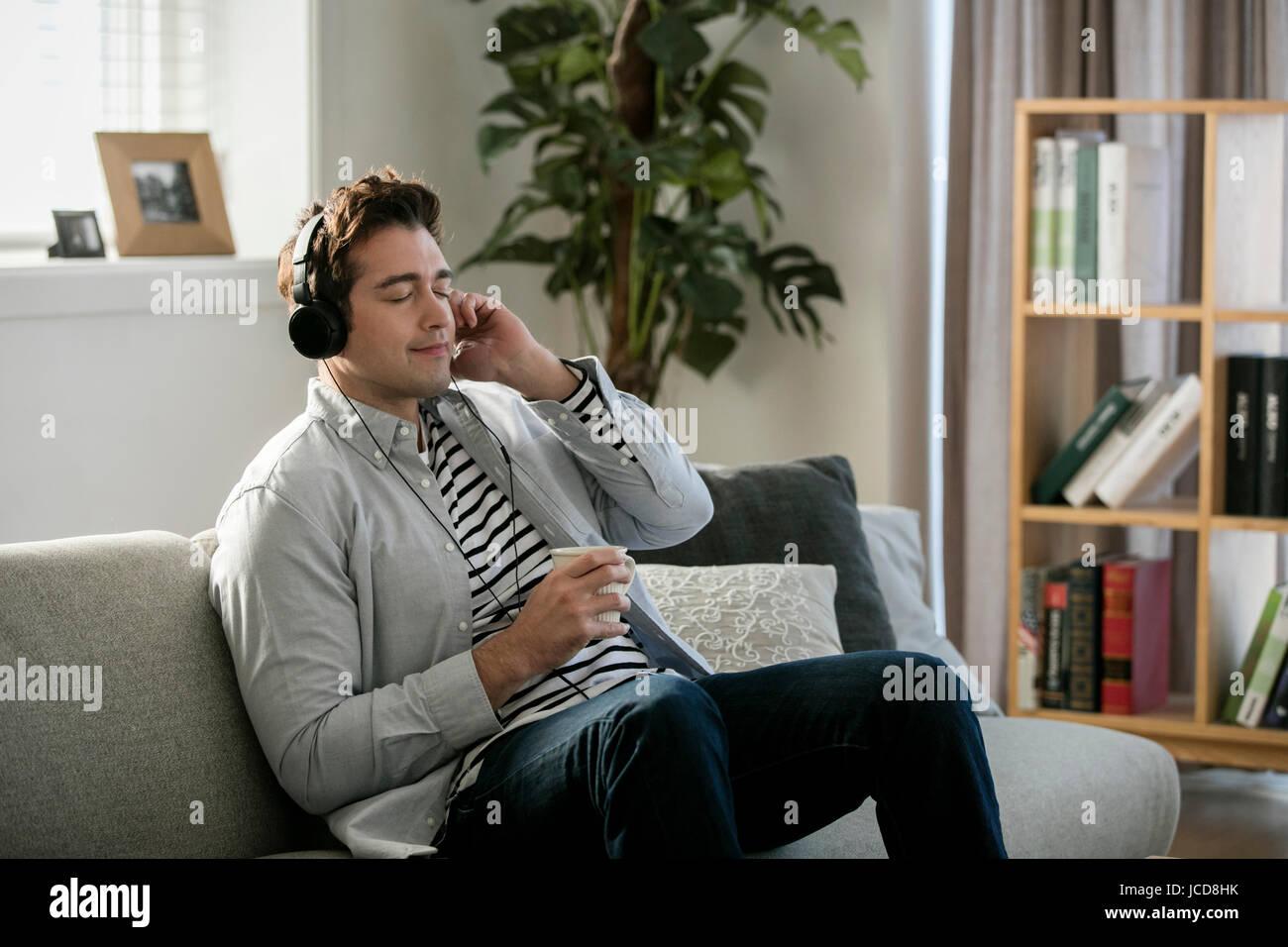 Lächelnde westlichen Mann in den Dreißigern auf Sofa anhören von Musik Stockbild