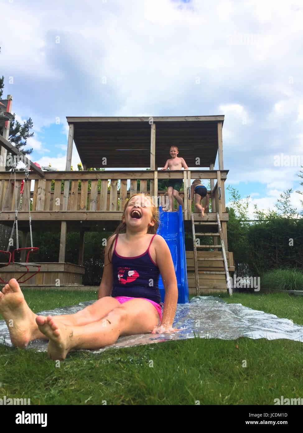 Kinder spielen auf einer Wasserrutsche im Garten im Sommer Stockbild
