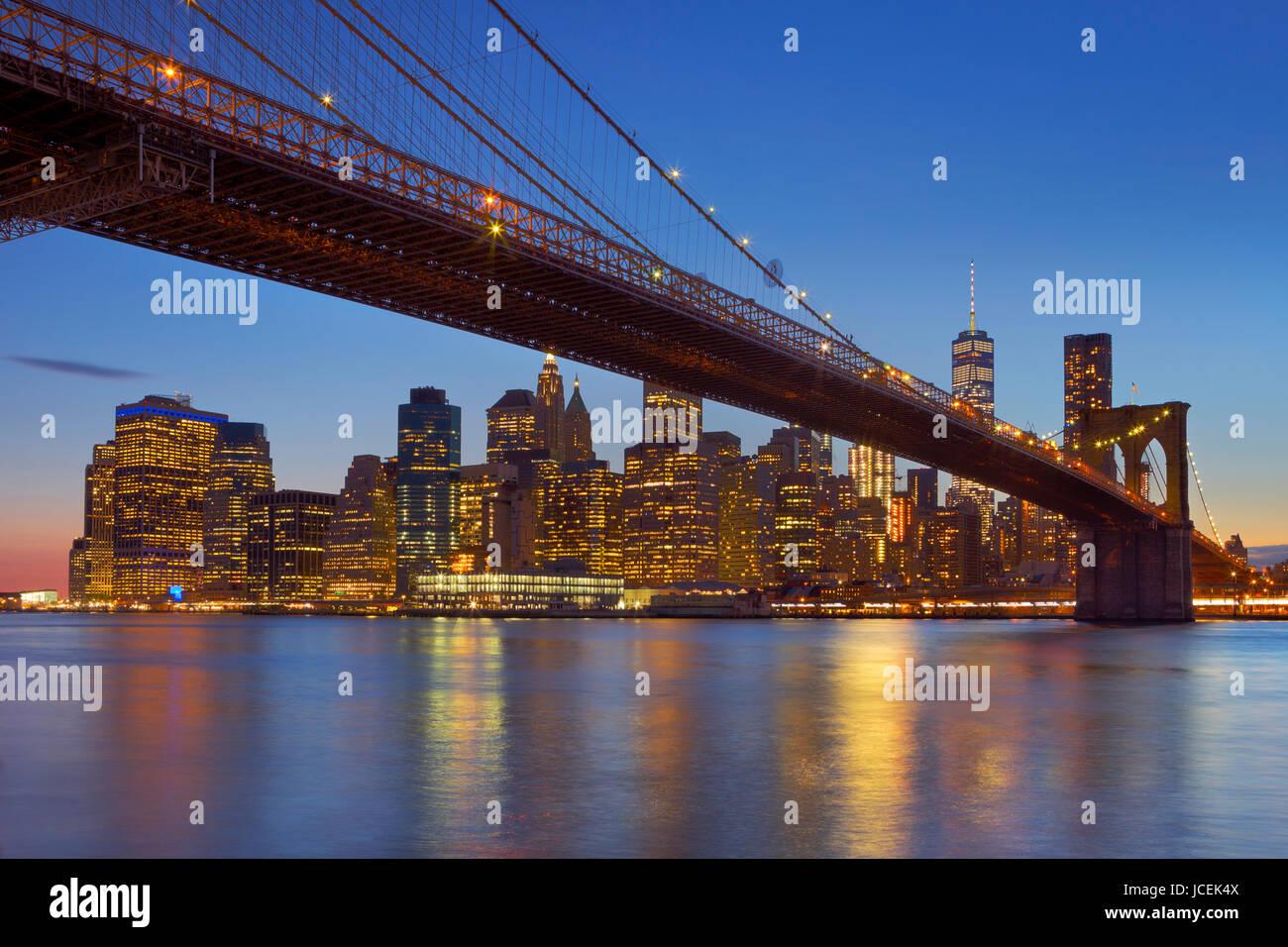 Brooklyn Bridge mit der New Yorker Skyline im Hintergrund, in der Dämmerung fotografiert. Stockbild