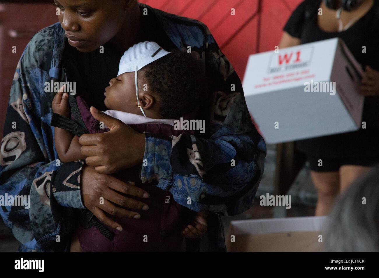 London, UK. 15. Juni 2017. Eine Frau hält ihr Kind wie sie Freiwillige Sortierung durch gespendete Kleidung am 15. Stockfoto