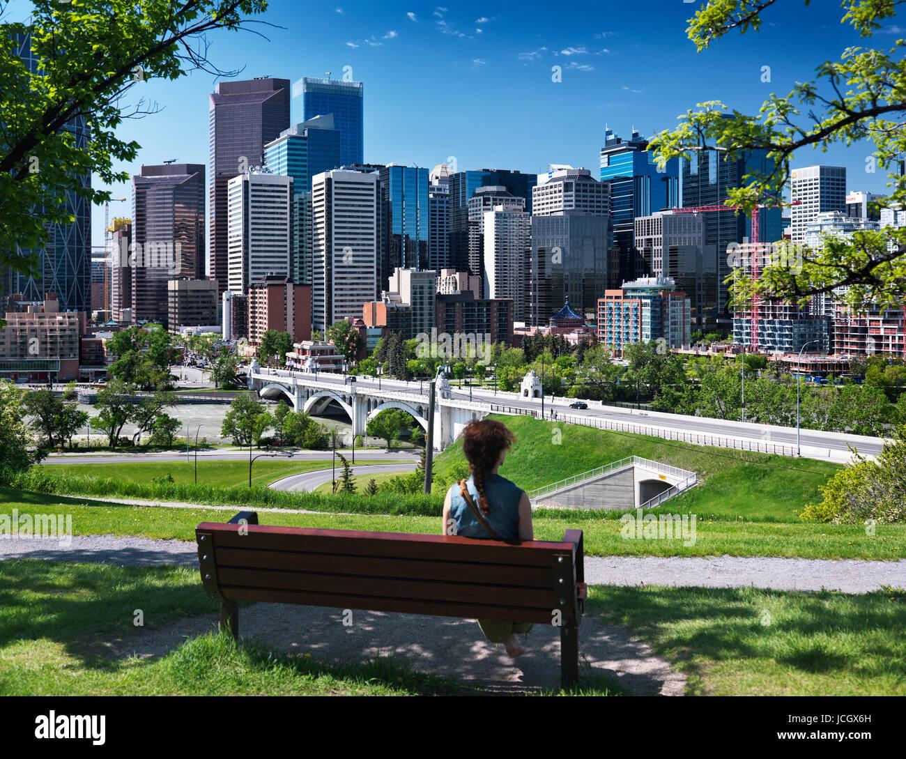 Junge Frau sitzt allein im Sunnyside Bank Park auf einer Bank an einem sonnigen Sommertag mit Centre Street Bridge Stockbild