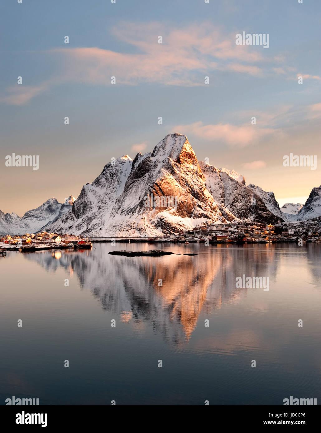 Mount Olstind spiegelt sich in den ruhigen Gewässern des Reinfjord auf den Lofoten-Inseln Stockfoto