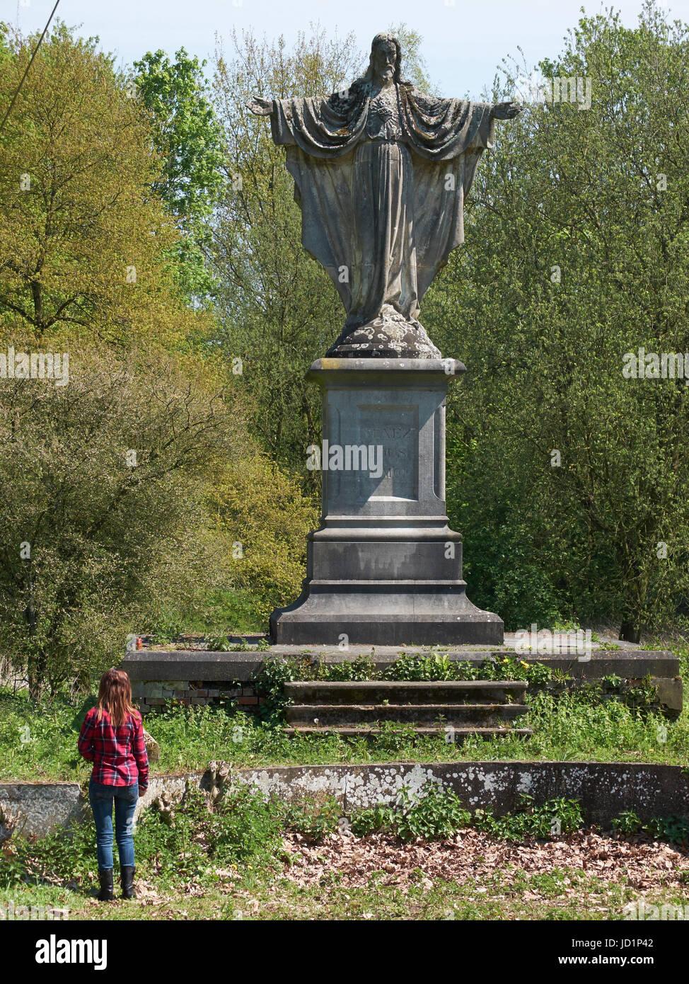Mädchen gehen vor einer Statue von Jesus Christus in einem verlassenen Park. Stockbild