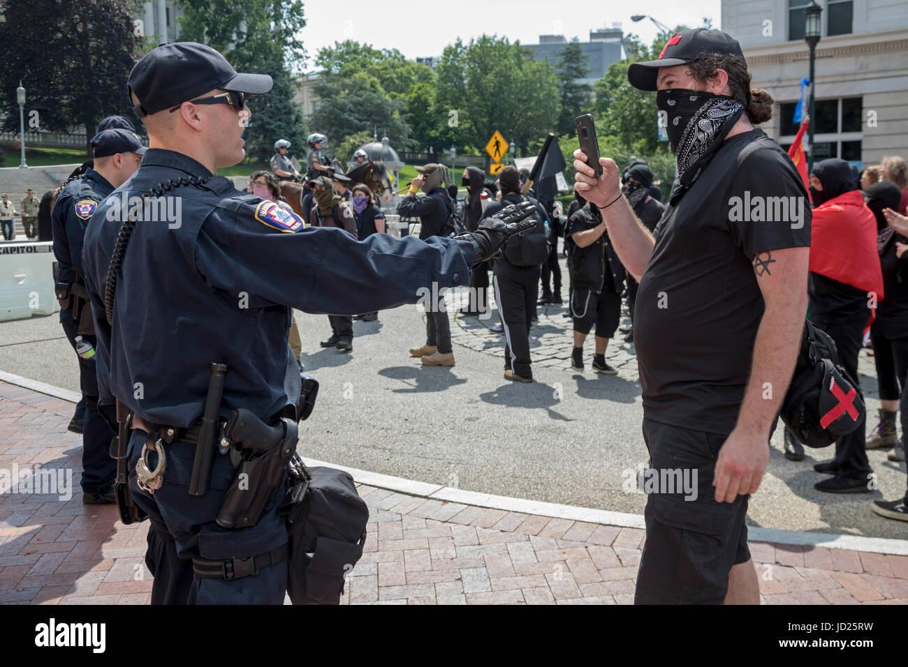 Harrisburg, Pennsylvania - A Black Bloc Anarchisten filmt ein Polizist während der Block Gegendemonstration Stockbild