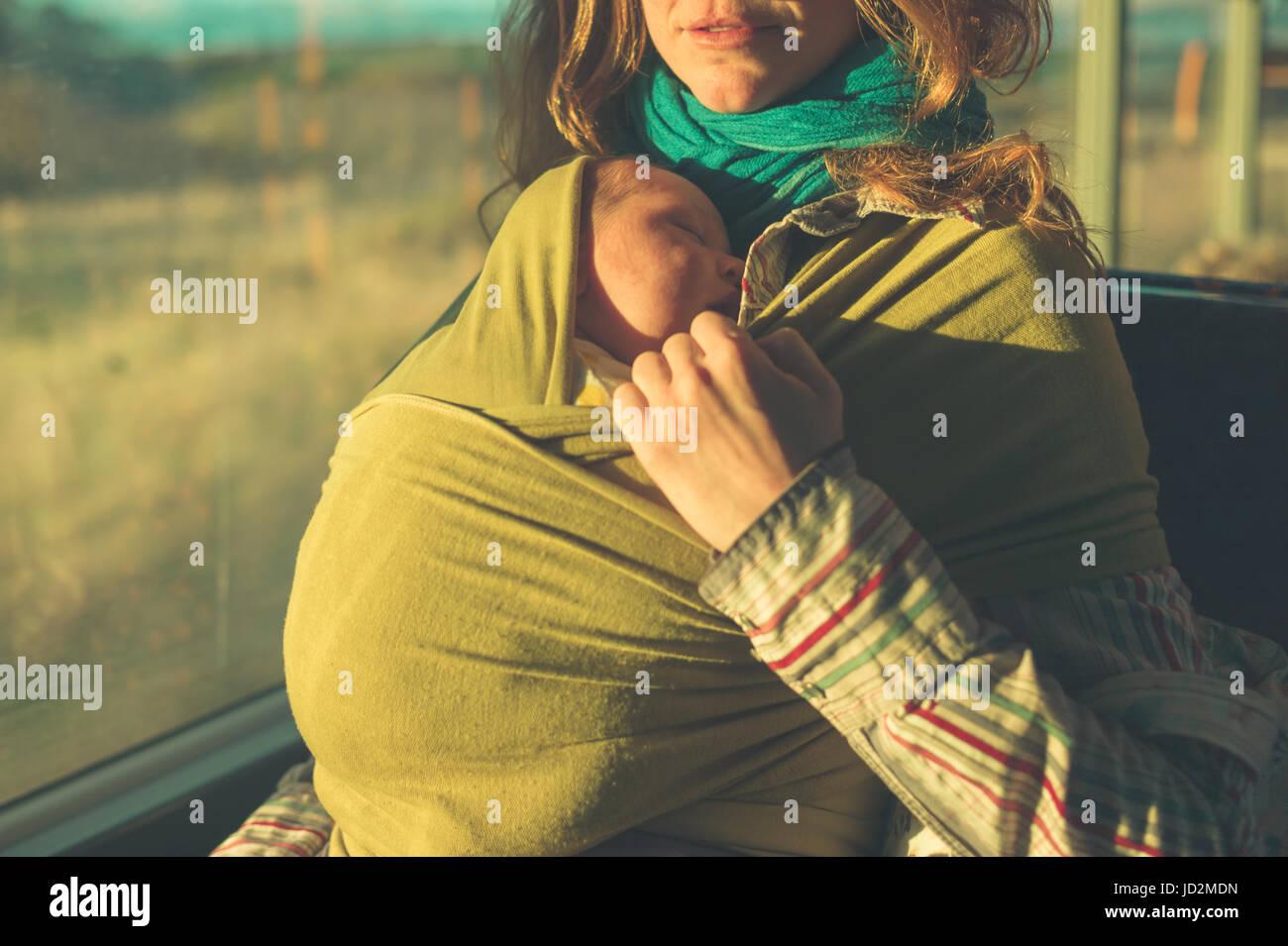 Am Bus ist eine junge Mutter mit ihrem Baby im Tragetuch bei Sonnenuntergang Stockbild