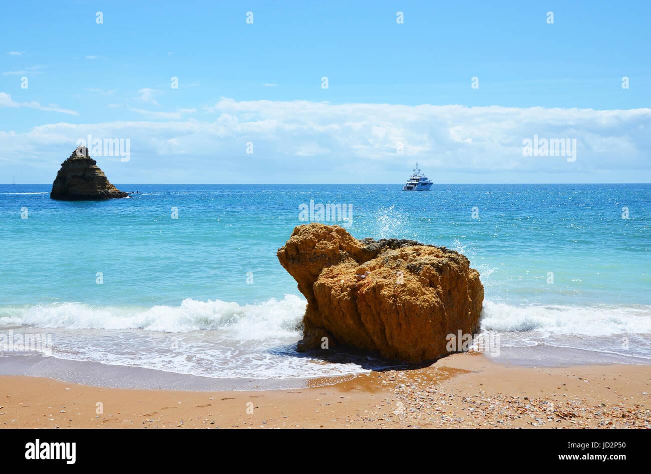 Wellen Waschen um einen Felsen am Praia Dona Ana und Yacht im Hintergrund, Algarve, Portugal Stockfoto
