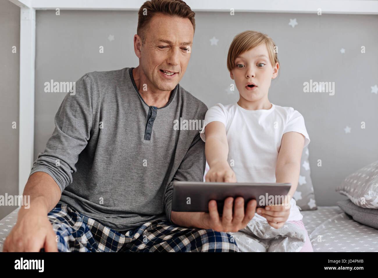Hell begeistert Kind zeigte auf dem tablet Stockbild