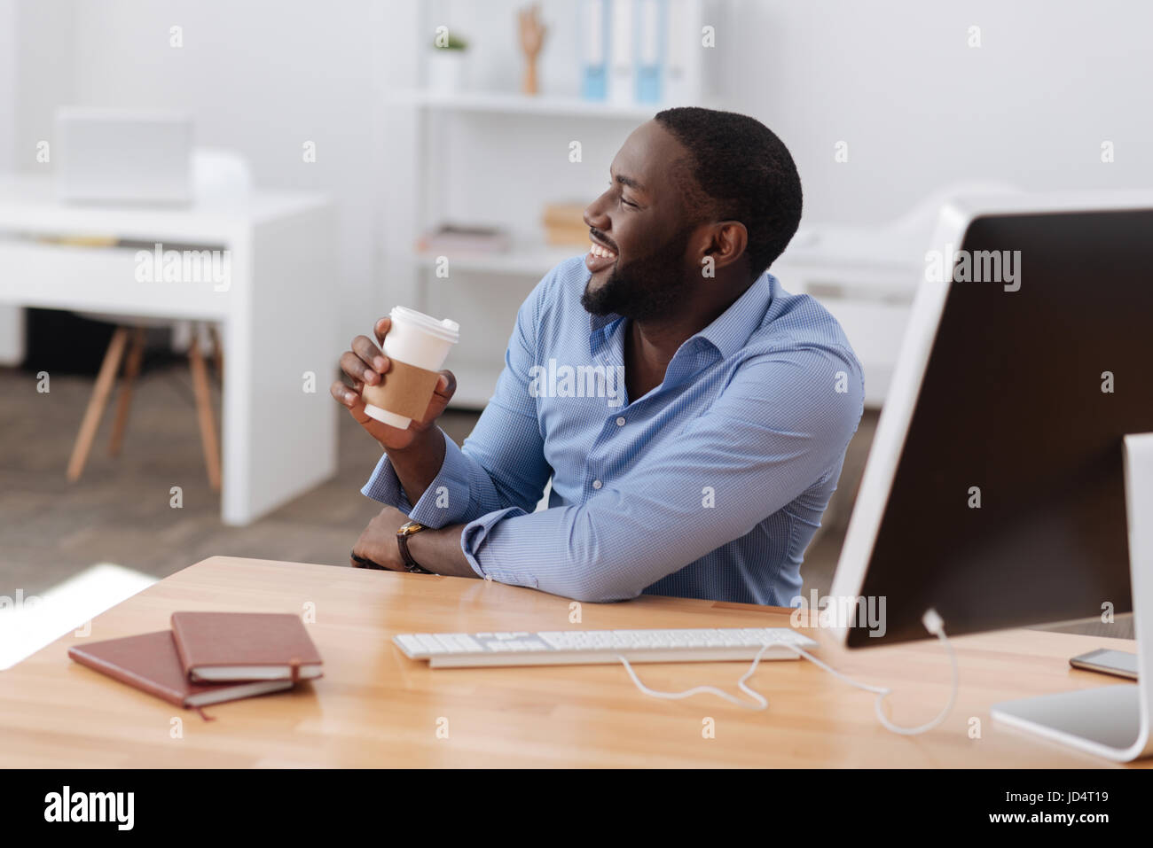 Glücklicher positiven Mann hält eine Tasse Kaffee Stockbild