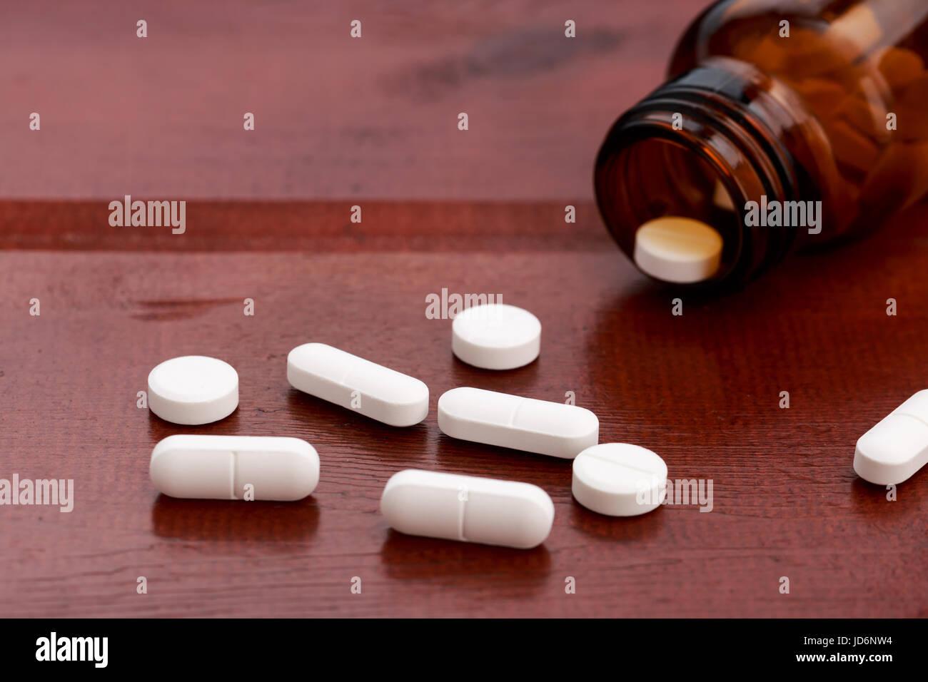 Braun Pillen, Flaschen und Haufen von weißen Pillen auf Holztisch Stockbild
