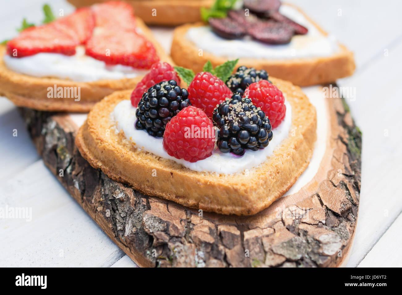 Herzförmige Kekse verteilt mit Quark, Erdbeeren, Brombeeren, Himbeeren, Kirschen und einem Zweig Minze präsentiert Stockbild
