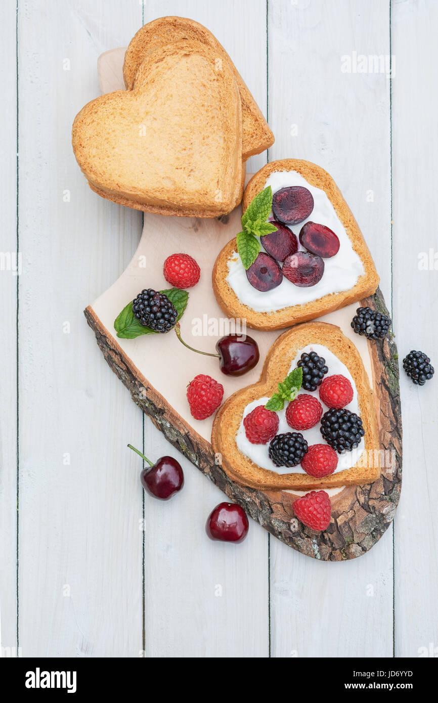 Herzförmige Kekse verteilt mit Quark, Kirschen und einem Zweig Minze präsentiert auf einem Baum Datenträger Stockbild