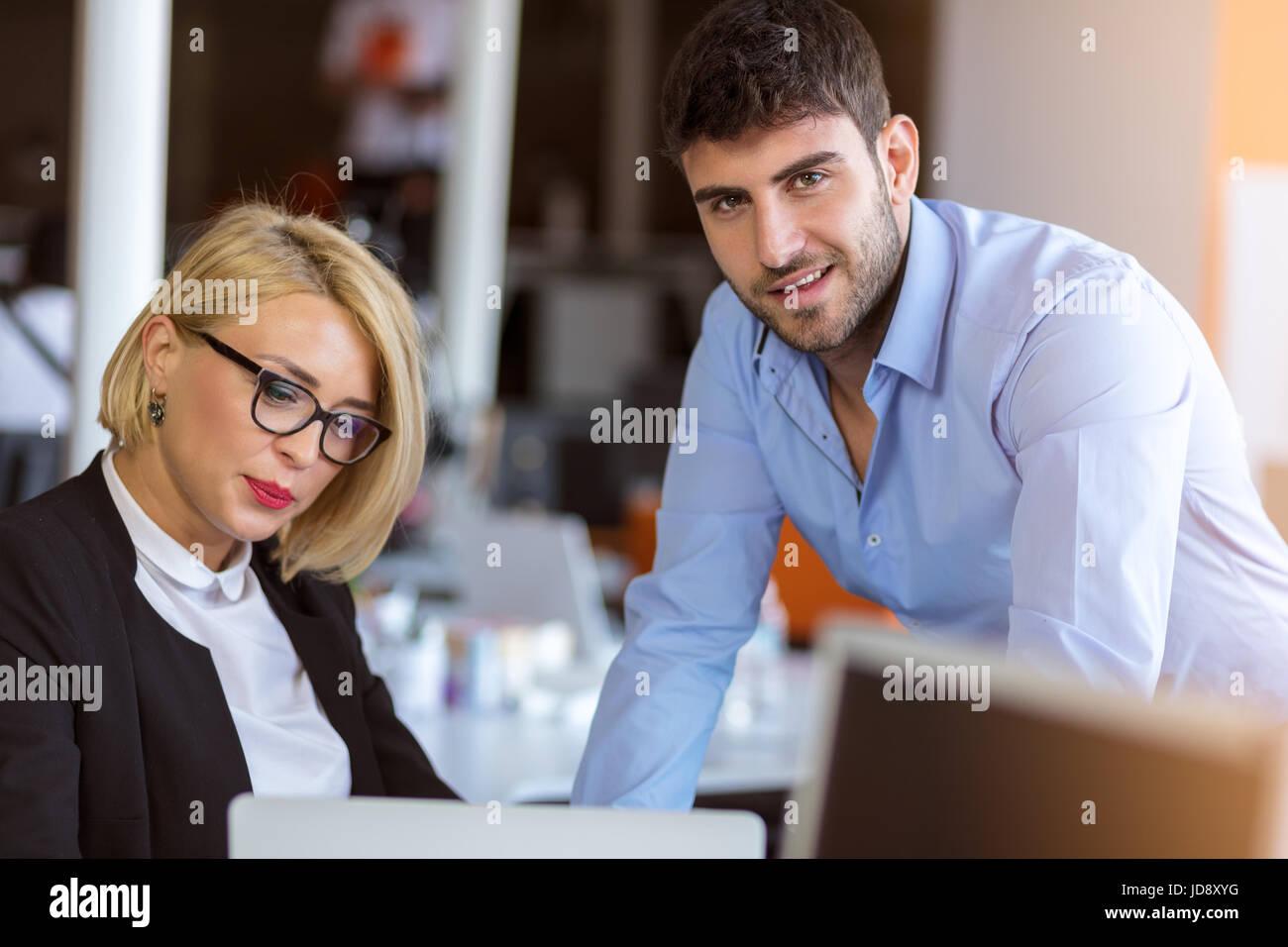 Kollegen unterhalten, zusammen sitzen am Bürotisch, Lächeln Stockfoto