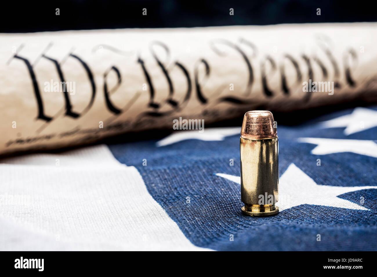 Die Verfassung der Vereinigten Staaten, die neben einer Kugel zusammengerollt ruht auf einer amerikanischen Flagge Stockbild