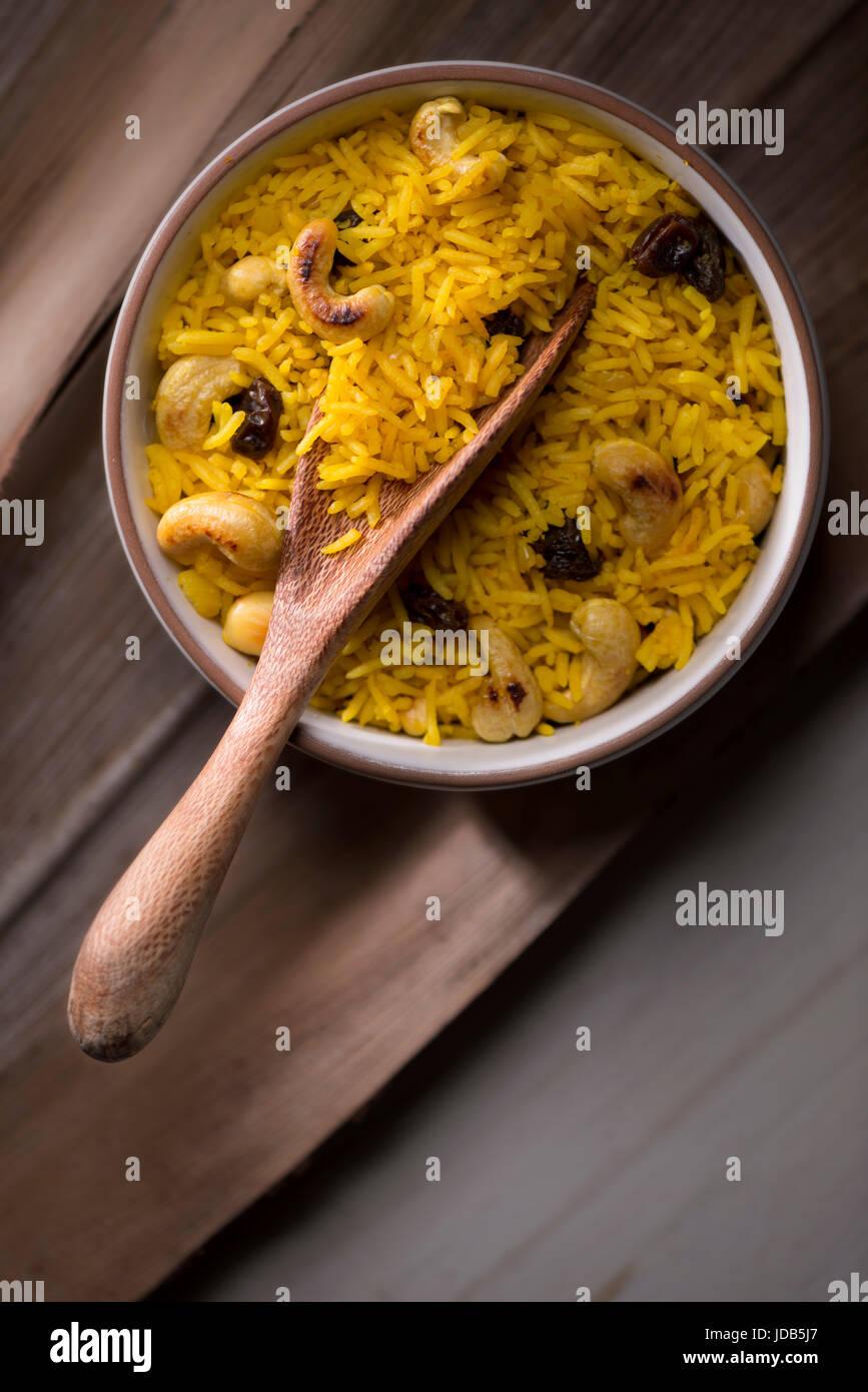 Kurkuma-Reis mit Boden Kurkuma gemacht, Basmati-Reis, Rosinen und Cashew-Nüssen, auf einem braunen Hintergrund. Stockbild