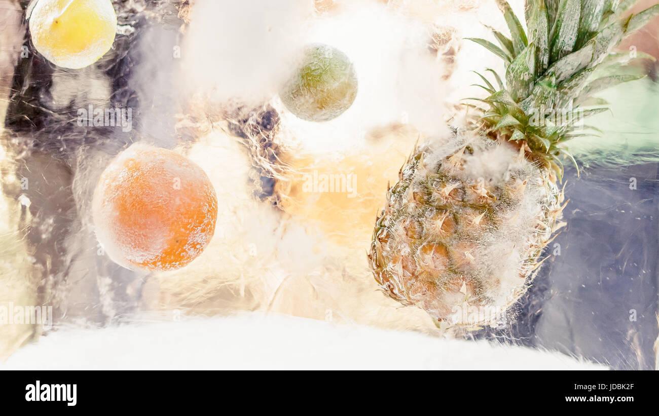 Eisblock mit gefrorene tropische Früchte, Ananas, Orange, Limone, Zitrone. Sommer-Erfrischung-Konzept Stockbild