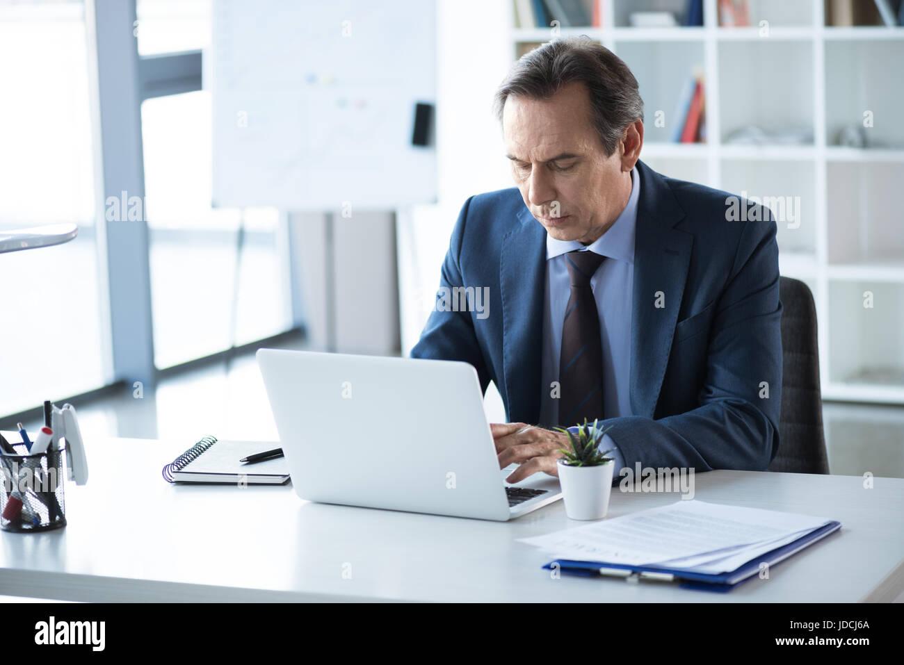 Reife ernsthaften Geschäftsmann arbeiten und tippen auf Laptop am Arbeitsplatz im Büro Stockbild