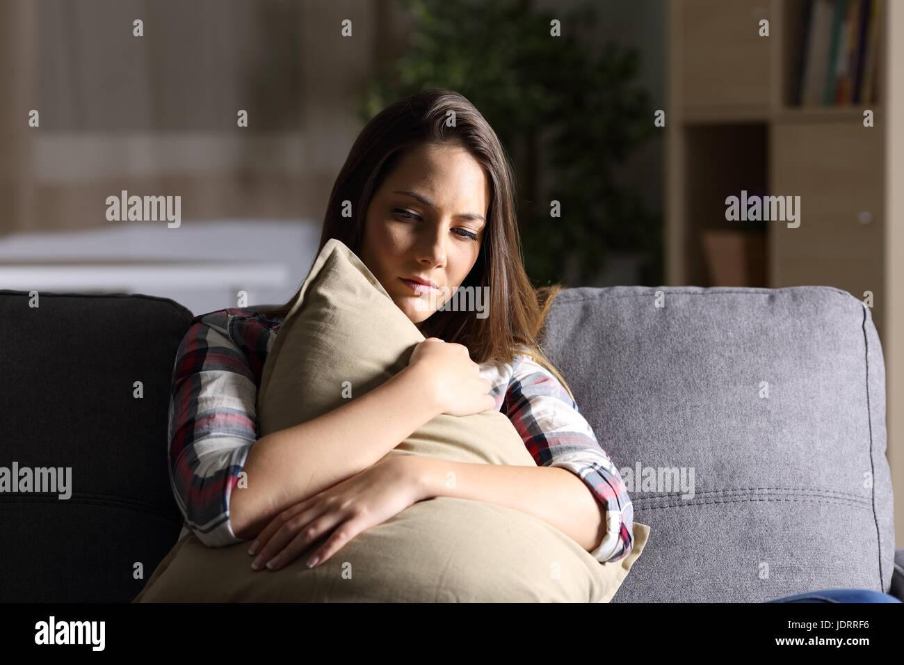 vorderansicht des ein trauriges m dchen umarmen eine kissen sitzen auf einer couch im wohnzimmer. Black Bedroom Furniture Sets. Home Design Ideas