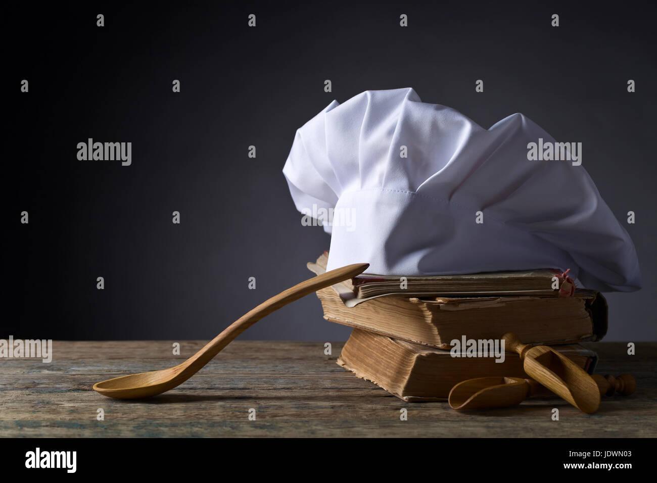 Alten Kulinarischen Büchern, Koch Hut Und Holzlöffel. Zubehör Für Die Küche  Auf Dem Alten Holztisch.