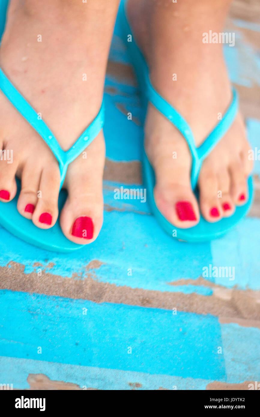 Lady die Füße mit rotem Nagellack in Sandalen auf dem sandigen Strand am Meer im Sommer auf Holzsteg. Stockfoto