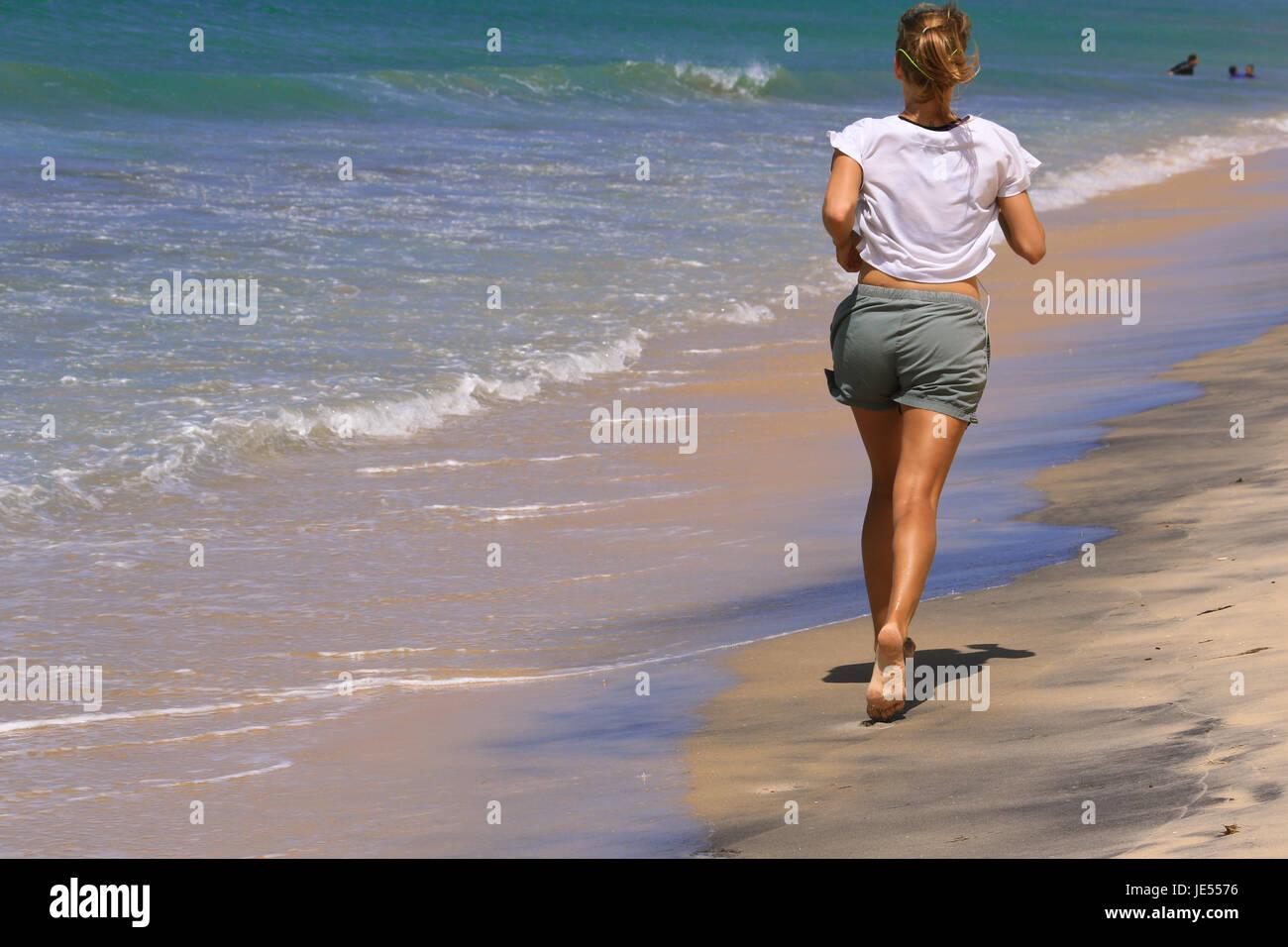 Sportliche Mädchen läuft am Strand des Ozeans für den perfekten Körper in Ordnung zu halten Stockbild