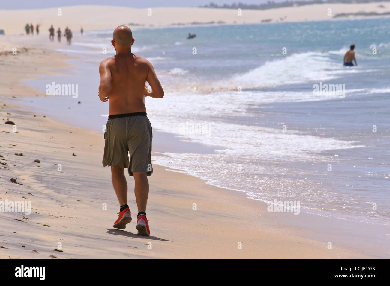 Sportlicher Mann läuft entlang des Strandes auf den Ozean für den perfekten Körper in Ordnung zu Stockbild