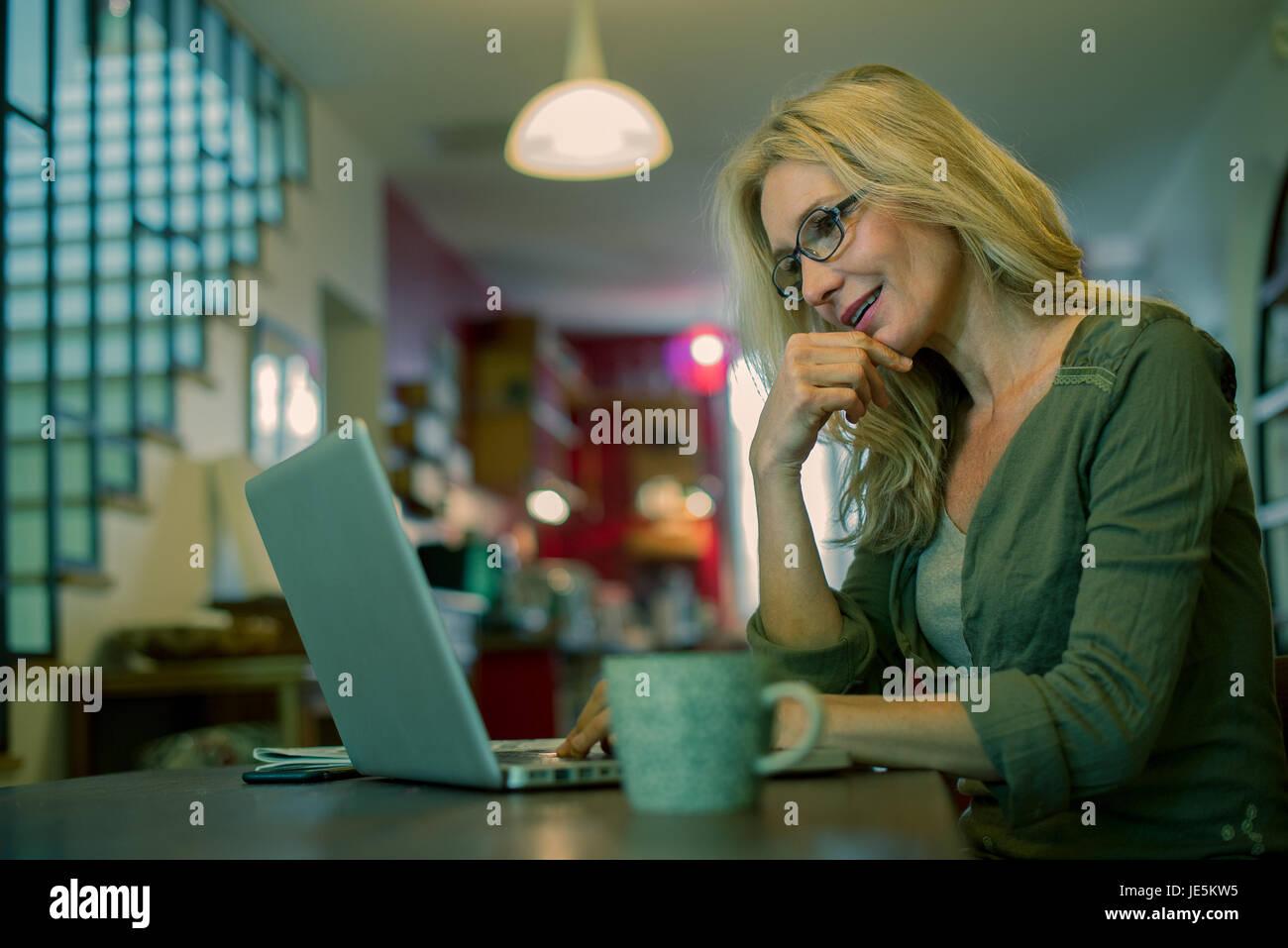 Frau mit Laptop-Computer zu Hause Stockfoto