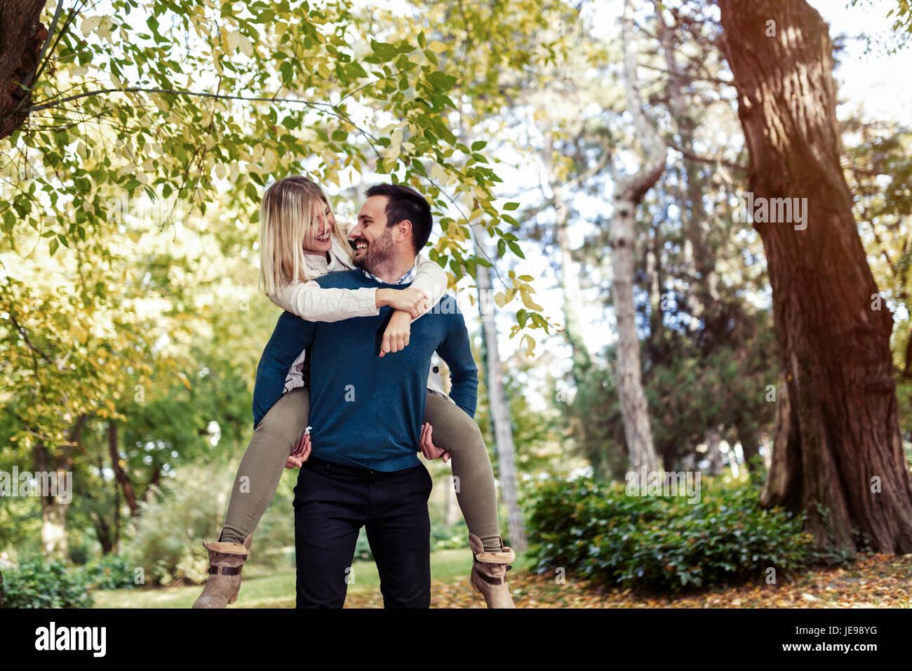 Gut aussehender Mann gibt seine beautful Freundin Huckepack Stockbild