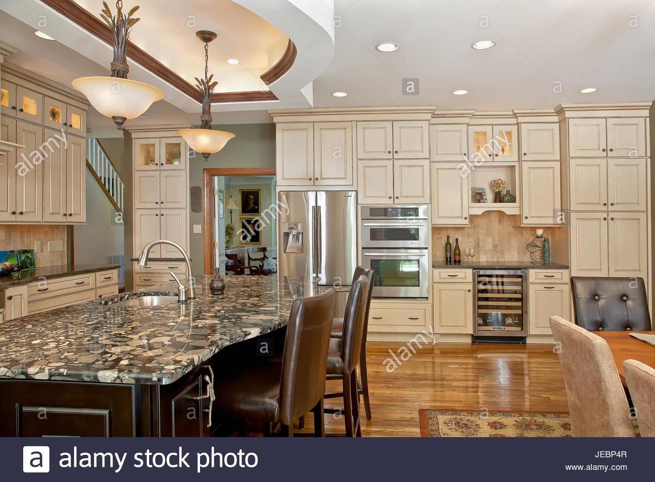 Große offene Küche mit Creme farbige Schränke, dunklen Holz Insel ...
