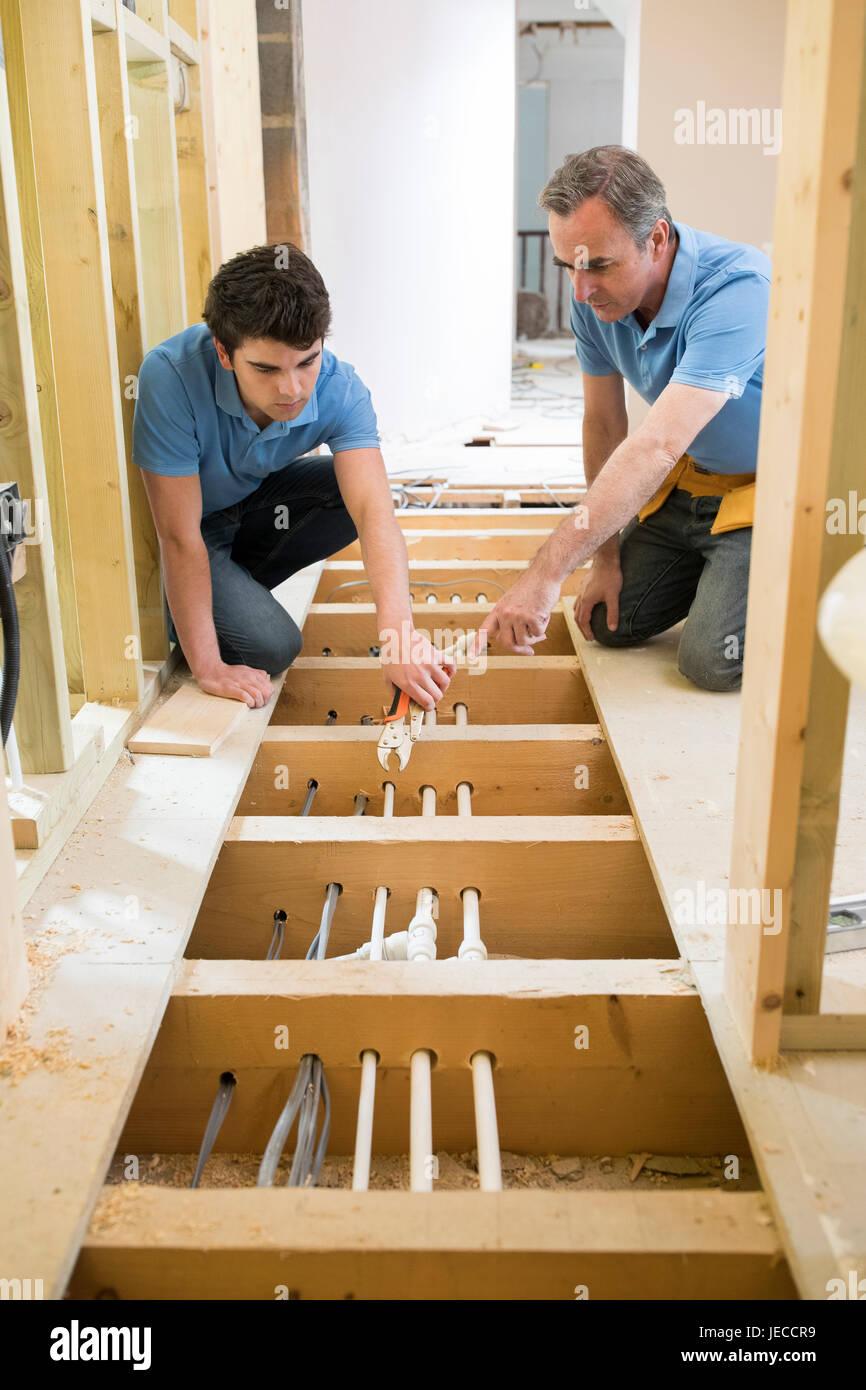 Klempner und Lehrling Einbau Zentralheizung Stockbild
