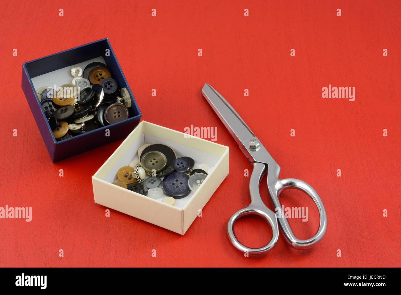 Sammlung von Schaltflächen in weißen und blauen Boxen und Metallscheren auf rotem Grund aus Holz Stockfoto