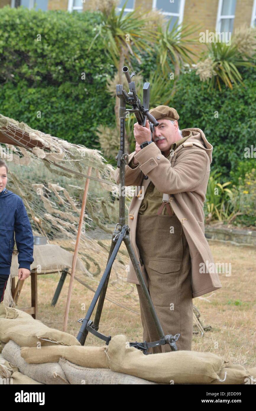 Mann in historischen Soldaten uniform zeigt über eine militärische Waffe auf die Streitkräfte Tag Stockbild