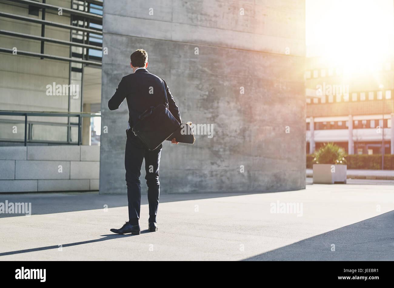 Rückansicht eines Geschäftsmannes in der Straße stehen und halten eine Skateboard. Stockbild