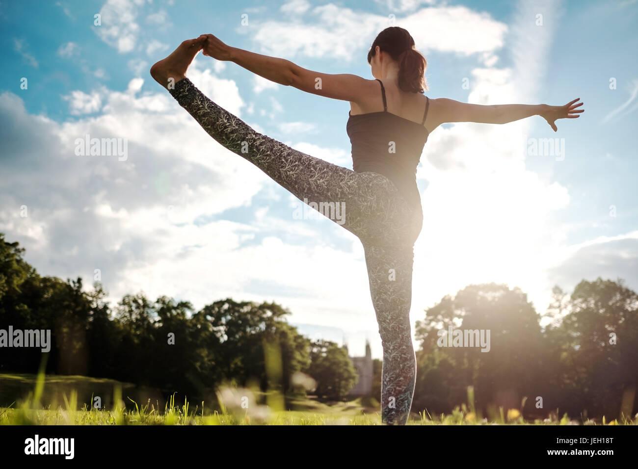 Kaukasische Frau im Yoga stehen Gleichgewicht Utthita Hasta Padangusthasana darstellen. Ansicht von hinten Stockbild