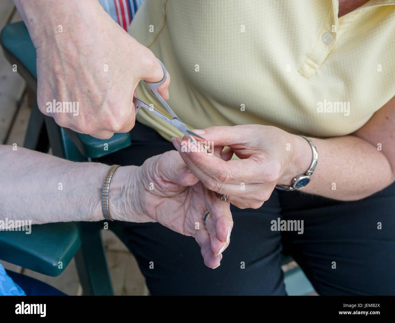 Eine ältere Frau Fingernägel trimmen: eine Frau mit Schere stutzt den Daumennagel eine ältere Frau Stockbild