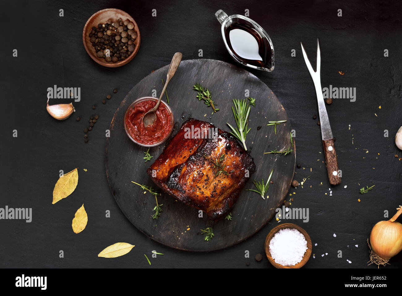 Gegrilltes Fleisch auf Holzbrett auf schwarzem Hintergrund, Ansicht von oben Stockbild