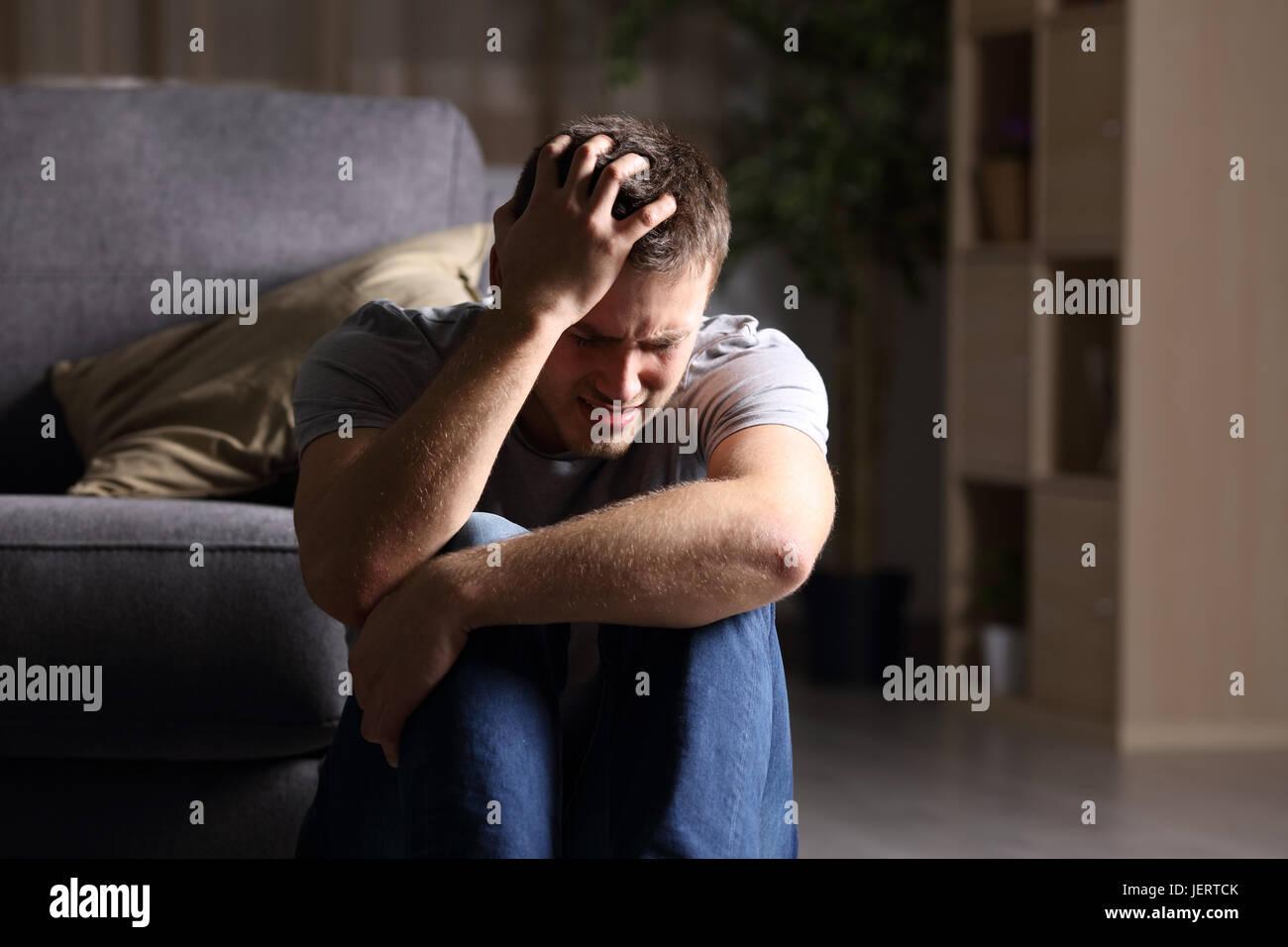 Trauriger Mann beklagt, sitzen auf dem Boden im Wohnzimmer in einem Haus mit einem dunklen Hintergrund indoor Stockbild