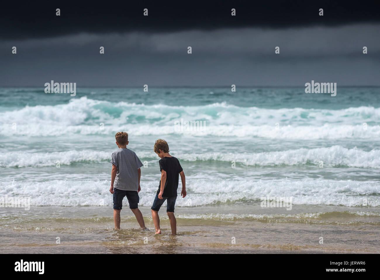 Dunkle Regenwolken Wolken als zwei junge Brüder Paddeln im Meer.  Wetter-UK. Stockfoto