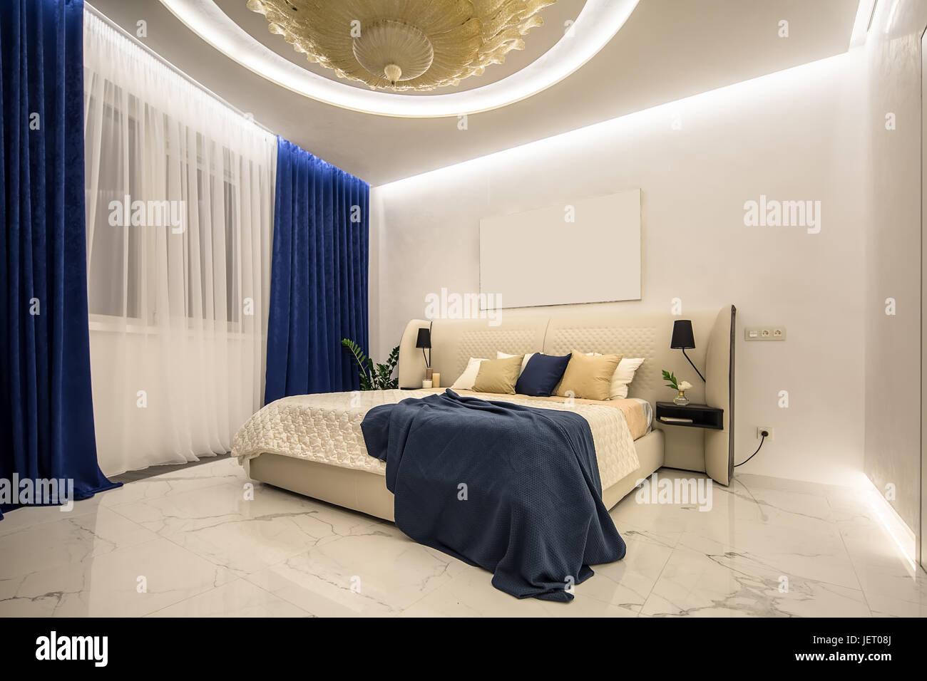 Beleuchtete Moderne Schlafzimmer Mit Einem Großen Phantasie Goldene  Kronleuchter An Der Decke. Es Ist Ein Beige Bett Mit Bunten Kissen Und Eine  Blaue Plaid, ...