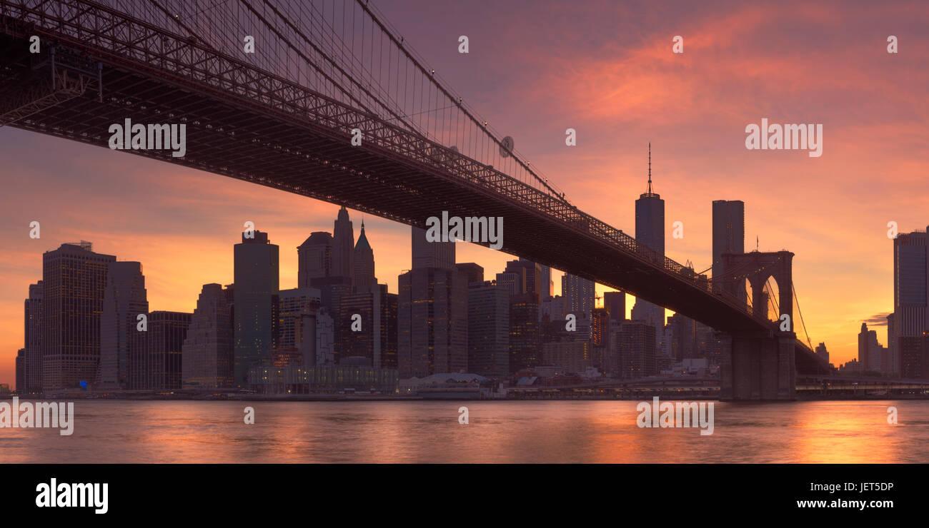 Brooklyn Bridge mit der New Yorker Skyline im Hintergrund, bei Sonnenuntergang fotografiert. Stockbild
