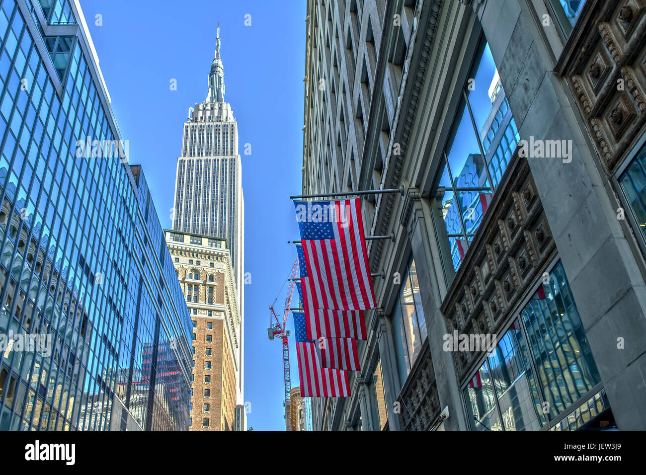 Empire State Building und US-Flagge Stockbild