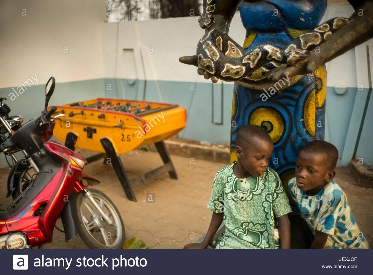 Jungen sitzen unter eine Python gehalten in den Händen einer Statue der angeblichen ersten Priesterin des Tempels Stockbild