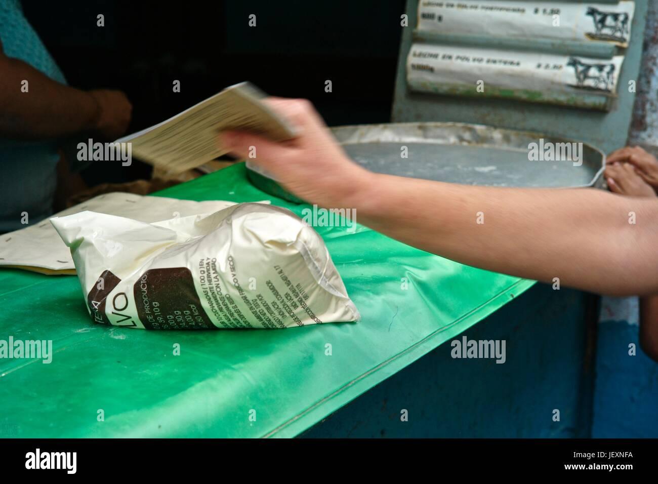 Eine kubanische präsentiert eine Rationierungskarte um grundlegende Produkte bei einer Ration-Shop zu erhalten. Stockbild