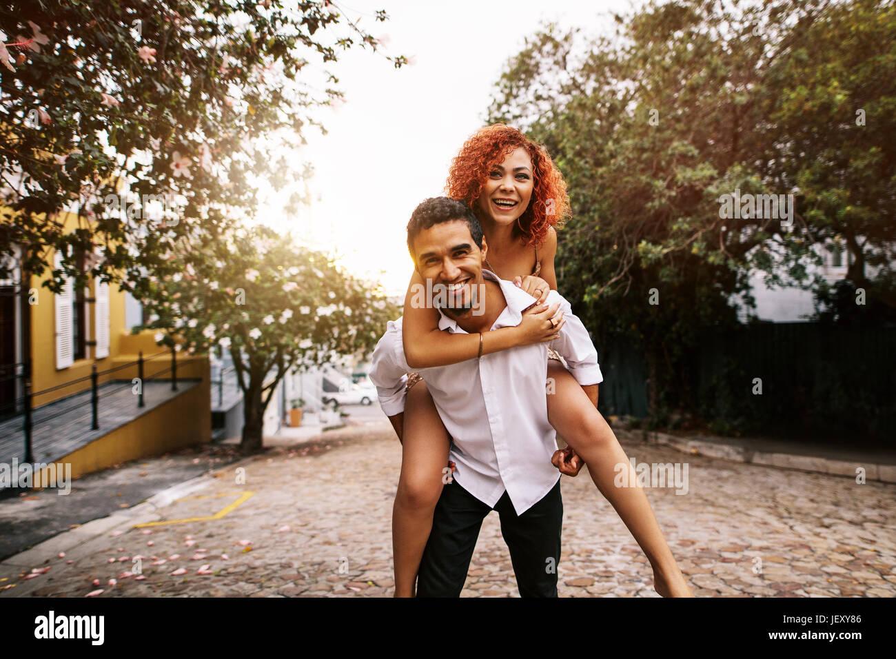 Junger Mann mit seiner Partnerin auf dem Rücken in einer spielerischen Stimmung während des Gehens auf Stockbild